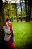 Мусульманская женщина говоря на телефоне и используя технологию Мусульманская женщина использует умный телефон Стоковое Изображение RF