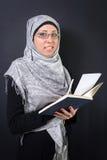 Мусульманская женщина держа книгу Стоковые Изображения