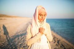 Мусульманская женщина на портрете духовности пляжа Всепокорная мусульманская женщина моля на пляже Летний отпуск, мусульманский и Стоковое Изображение RF