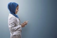 Мусульманская женщина печатая на мобильном телефоне Стоковые Изображения