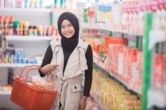 Мусульманская женщина покупая некоторый халяльный продукт Стоковое Фото
