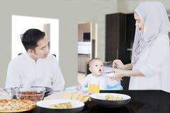 Мусульманская женщина подавая ее младенец Стоковые Изображения RF