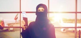 Мусульманская женщина с билетом и пасспорт на авиапорте Стоковое фото RF