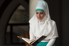 Мусульманская женщина читает Koran Стоковое Изображение