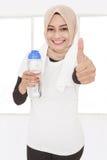 Мусульманская sporty женщина держа бутылку минеральной воды и давать Стоковое Изображение