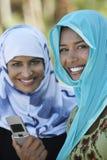 Мусульманские женщины с мобильным телефоном Стоковая Фотография