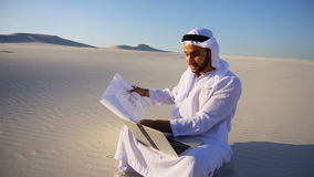 Мусульманский архитектор шейха ОАЭ аравийца сидя с компьтер-книжкой на песке в пустыне на горячий летний день сток-видео