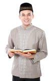 Мусульманский человек держа Коран стоковое изображение