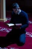 Мусульманский человек читая Koran в мечети Стоковое Фото