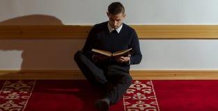 Мусульманский человек читая Koran в мечети Стоковое фото RF
