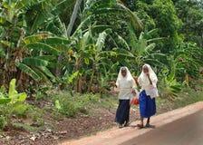 2 мусульманских школьницы в головных платках идут вдоль дороги в джунглях Стоковые Фотографии RF