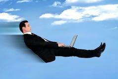 Муха бизнесмена используя компьютер Стоковые Фото