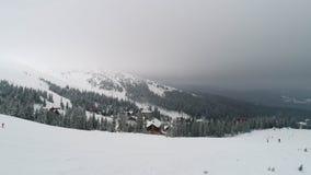 Муха над наклоном горы с лыжниками видеоматериал