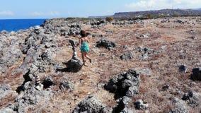 Муха трутня над женщиной бежать на seashore, Крите сток-видео
