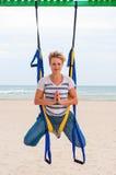 Мух-йога, анти- сила тяжести или йога мухы на пляже Молодая женщина делая тренировку йог Йога с гамаком морем представление Стоковые Фото