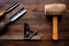 Мушкел и установленный квадрат с деревянными зубилами на старой столешнице Стоковое Изображение RF