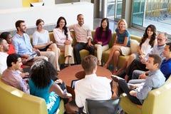 Мульти-культурный конторский персонал сидя имеющ встречать совместно Стоковые Изображения