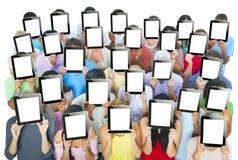 Мульти-этническая группа людей держа таблетки цифров Стоковые Изображения