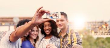 Мульти-этническая millenial группа в составе друзья принимая фото selfie с мобильным телефоном на terrasse крыши на заход солнца Стоковое Изображение RF