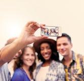 Мульти-этническая millenial группа в составе друзья принимая фото selfie с мобильным телефоном на terrasse крыши на заход солнца Стоковые Фото