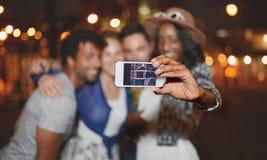 Мульти-этническая millenial группа в составе друзья принимая фото selfie с мобильным телефоном на terrasse крыши используя вспышк Стоковое фото RF