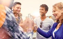 Мульти-этническая millenial группа в составе друзья partying и наслаждаясь пиво на terrasse крыши на заходе солнца Стоковые Фотографии RF