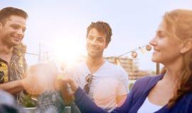 Мульти-этническая millenial группа в составе друзья partying и наслаждаясь пиво на terrasse крыши на заходе солнца Стоковые Изображения RF