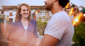 Мульти-этнические millenial пары flirting пока имеющ питье на патио крыши на заходе солнца Стоковая Фотография