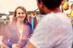 Мульти-этнические millenial пары flirting пока имеющ питье на патио крыши на заходе солнца Стоковое Изображение RF