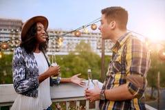 Мульти-этнические millenial пары flirting пока имеющ питье на патио крыши на заходе солнца Стоковые Изображения RF