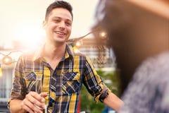 Мульти-этнические millenial пары flirting пока имеющ питье на terrasse крыши на заходе солнца Стоковое Изображение