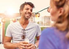 Мульти-этнические millenial пары flirting пока имеющ питье на terrasse крыши на заходе солнца Стоковые Фотографии RF
