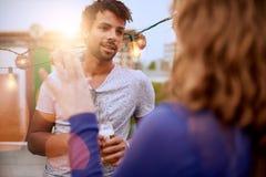 Мульти-этнические millenial пары flirting пока имеющ питье на terrasse крыши на заходе солнца Стоковое Фото