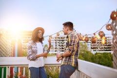 Мульти-этнические millenial пары flirting пока имеющ питье на terrasse крыши на заходе солнца Стоковые Изображения RF