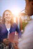Мульти-этнические millenial пары flirting пока имеющ питье на terrasse крыши на заходе солнца Стоковая Фотография