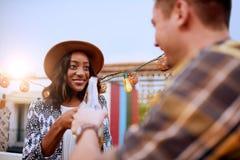 Мульти-этнические millenial пары flirting пока имеющ питье на terrasse крыши на заходе солнца Стоковые Фото