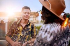 Мульти-этнические millenial пары flirting пока имеющ питье на terrasse крыши на заходе солнца Стоковые Изображения