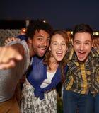 Мульти-этнические millenial друзья принимая внезапное selfie с мобильным телефоном на патио крыши Стоковые Фотографии RF