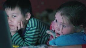 Мульти-этнический мальчик и белая девушка лежа на кресле наблюдая тетрадь в темноте 4K видеоматериал