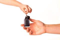 Мыжская рука держа ключ автомобиля и вручая его сверх Стоковые Фото