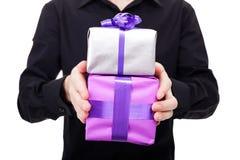 Мыжская рука держит серебряный подарок над белой предпосылкой Стоковые Фотографии RF