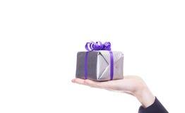Мыжская рука держит серебряный подарок Стоковое Изображение RF