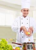 Мыжской шеф-повар положил некоторый ингридиент в лоток Стоковые Фото