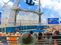 Мыс Канаверал, США - 3-ье мая 2018: Люди сидя на выставке на амфитеатре театра Aqua на оазисе вкладыша круиза  Стоковые Фотографии RF