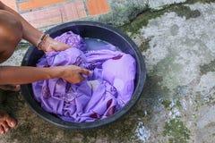 Мытье женщины вручает пакостные одежды в черноте таза для очищать стоковые фотографии rf