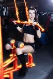 Мышечная девушка фитнеса брюнет делая тренировки в спортзале Весы девушки фитнеса поднимаясь на машине для культуристов Стоковое фото RF
