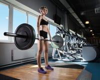 Мышечная женщина в спортзале делая тяжеловесные тренировки стоковое фото rf