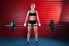 Мышечная женщина в спортзале делая тяжеловесные тренировки стоковые изображения