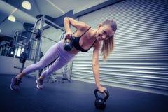 Мышечная женщина делая pushups с kettlebells Стоковое Фото