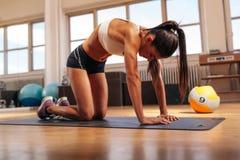 Мышечная женщина работая на циновке фитнеса Стоковые Изображения RF